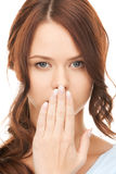 Woman with hand over mouth Stock Photo
