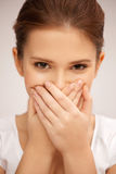 Woman with hand over mouth Stock Images