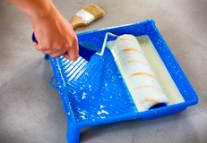 Woman hand with paint roller and paint tray with primer. Royalty Free Stock Images