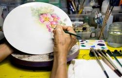 Woman hand painting ceramic plate Stock Photos