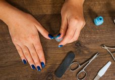 Woman hand painting her nails with nail polish on a wooden background. top view Royalty Free Stock Photography