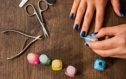 Woman hand painting her nails with nail polish on a wooden background. top view Stock Image