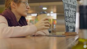 Woman hand with paper cup of coffee using smartphone. Closeup of woman hand with paper cup of takeaway coffee using smartphone touch screen stock footage