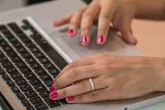 Woman hand on pc. Woman hands with red nails working on a computer keyboard Stock Images