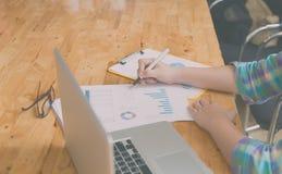 Woman hand, pen, glasses, business document, laptop computer   Stock Images