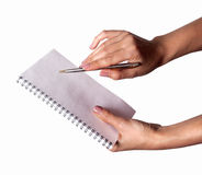 Woman hand with pen and notebook. On a white background Royalty Free Stock Photo