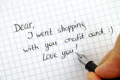 Woman hand with pen wriring note - Dear, I went shopping with  y. Our credit card. Love you Royalty Free Stock Images