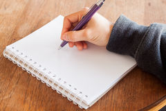 Woman hand with pen writing on notebook Stock Photography