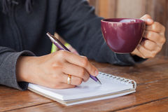Woman hand with pen writing on notebook Royalty Free Stock Images