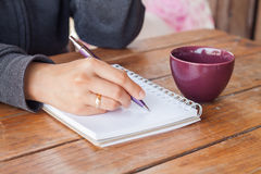 Woman hand with pen writing on notebook Stock Images