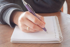 Woman hand with pen writing on notebook Royalty Free Stock Photo