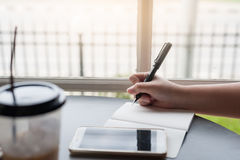 Woman hand with pen writing on notepad Stock Images