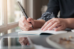 Woman hand with pen writing on notepad Stock Photography