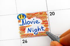 Woman hand with pen writing reminder Movie Night in calendar. Royalty Free Stock Photography