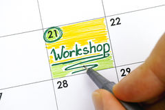 Woman hand with pen writing reminder Workshop in calendar. Woman hand with green pen writing reminder Workshop in calendar royalty free stock photo