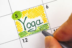 Woman hand with pen writing reminder Yoga in calendar Royalty Free Stock Photo