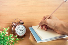 Woman hand with pencil on book and clock Stock Image