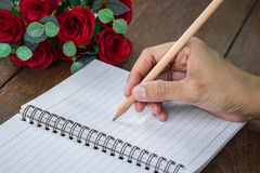 Woman hand with pencil writing on notebook Stock Images