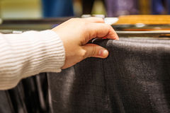 Woman'hand pick pick trousers in a store Stock Images