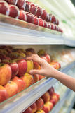 Woman hand picking apples from supermarket shelf Royalty Free Stock Photos