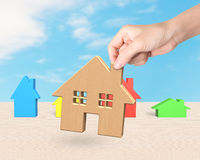 Woman hand picking wooden house Royalty Free Stock Images