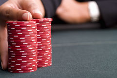 Woman with hand on pile of gambling chips, close-up Stock Images