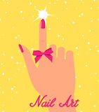 Woman hand with pink fingernails and pink bow on yellow background.  Stock Images