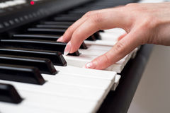 Woman hand playing a MIDI controller keyboard synthesizer close up.  Stock Images