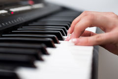 Woman hand playing a MIDI controller keyboard synthesizer close up.  Royalty Free Stock Image