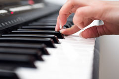 Woman hand playing a MIDI controller keyboard synthesizer close up.  Stock Photo