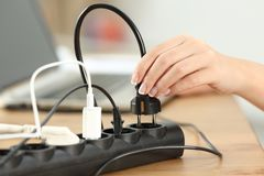 Woman hand plugging a plug in an electrical socket. Close up of a woman hand plugging a plug in an electrical socket on a table at home Stock Photo