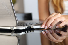 Woman hand plugging an usb  pendrive on a laptop at home. Close up of a woman hand plugging an usb  pendrive on a laptop at home Royalty Free Stock Image
