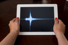 Woman hand pointing a blue earthquake on a tablet Royalty Free Stock Photo