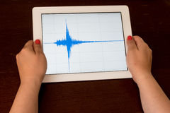 Woman hand pointing a blue earthquake on a tablet Royalty Free Stock Image