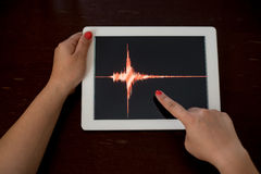 Woman hand pointing a red earthquake on a tablet Royalty Free Stock Image