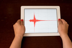 Woman hand pointing a red earthquake on a tablet Royalty Free Stock Photo