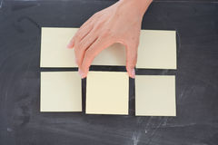 Woman hand posting empty adhesive notes on blackboard Stock Image