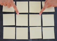 Woman hand posting empty adhesive notes on blackboard Royalty Free Stock Photography