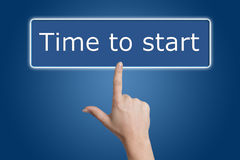 Pressing time to start button. Woman hand pressing a button with word  Time to start  on blue background Stock Photo