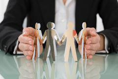 Woman Hand Protecting Cut-out Figures Royalty Free Stock Photos