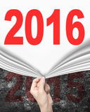 Woman hand pulling new 2016 curtain covering old 2015 wall Stock Image