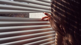 Woman hand pushing the blinds and looking out window stock video footage