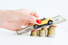Woman hand pushing a toy car over a stack of coins Royalty Free Stock Photo