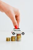 Woman hand pushing a toy car over a stack of coins Stock Photos