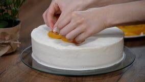 Woman hand put peach on the cake crust. Woman hand put fresh peach on the cake crust stock footage