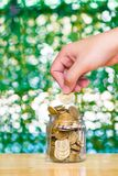 Woman hand put gold coin money in the glass jar on table in gard. En with green background, for saving for the future banking finance business concept Royalty Free Stock Images