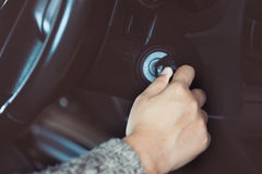 Woman hand put key into the ignition and starts the car engine Stock Image
