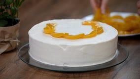 Woman hand put peach on the cake crust.  stock video
