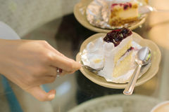 Woman hand put pudding on the cake crust Stock Photo