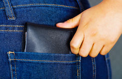 Woman hand putting a black wallet inside of jeans back pocket Royalty Free Stock Photos